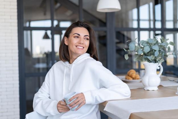 自宅のキッチンで暖かい白いパーカーを着た若い女性は、一杯のコーヒーで一日を始めます