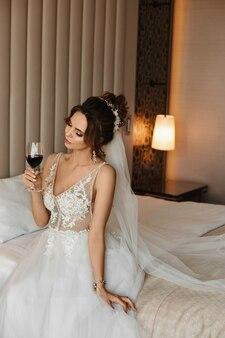Молодая женщина в свадебном платье пьет вино