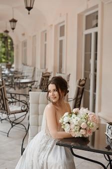 屋外のテーブルに座っている花束を持つウェディング ドレスを着た若い女性