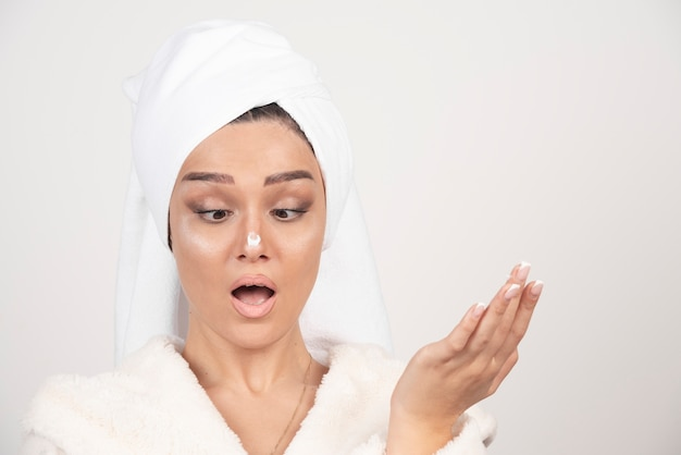 그녀의 코에 크림을 적용하는 흰 가운에 젊은 여자