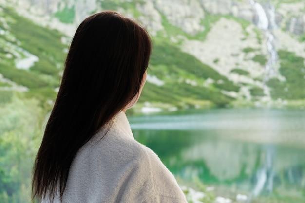 Молодая женщина в белом халате смотрит в окно с прекрасным видом на горы