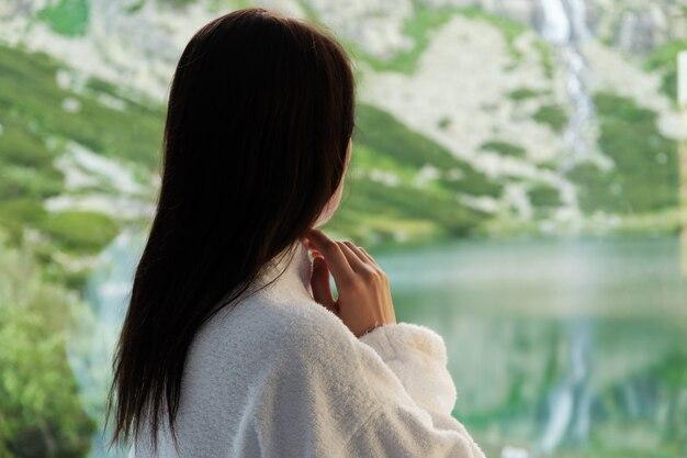 Молодая женщина в белом халате смотрит в окно с прекрасным видом