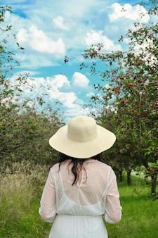 Молодая женщина в белом платье и шляпа стоя в вишневом саду сельские пейзажи