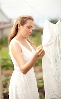 Молодая женщина в белом платье вешает белье на открытом воздухе