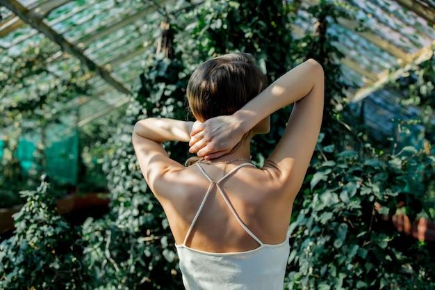 아이비와 온실에서 흰 드레스에 젊은 여자