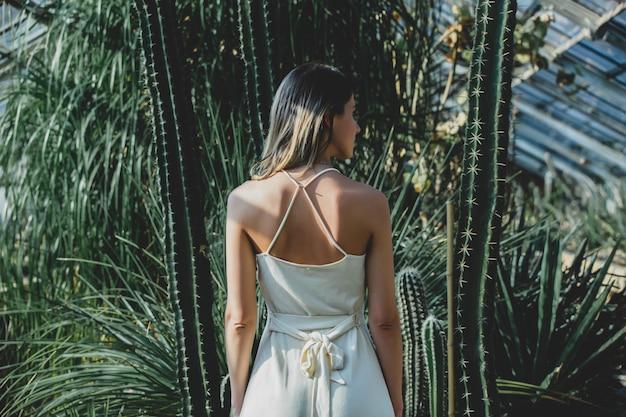다육 식물과 온실에서 흰 드레스에 젊은 여자