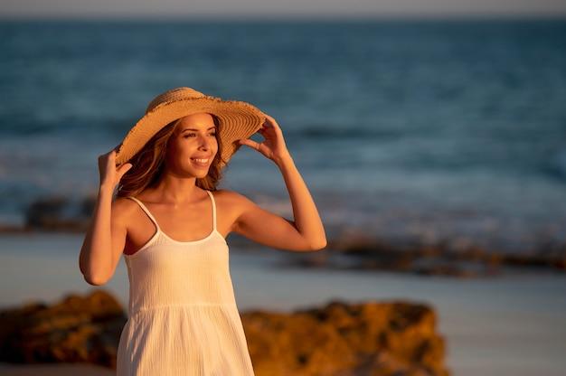 海の横に白いドレスを着た若い女性