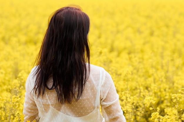 Молодая женщина в белом платье, стоя в поле рапса
