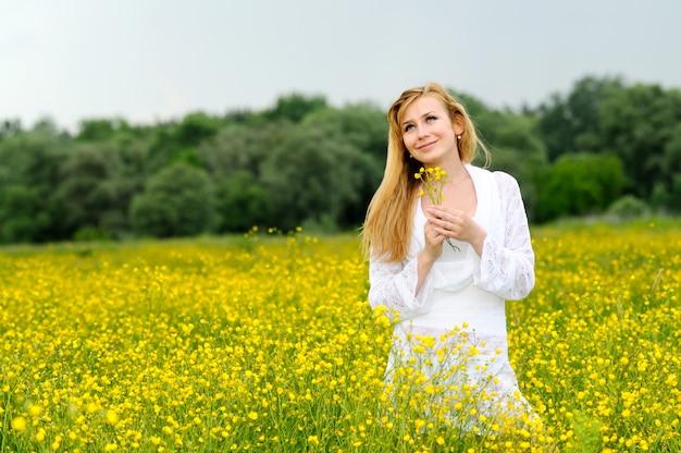 그녀의 손에 꽃과 함께 포즈 흰색 레이스 드레스에 젊은 여자
