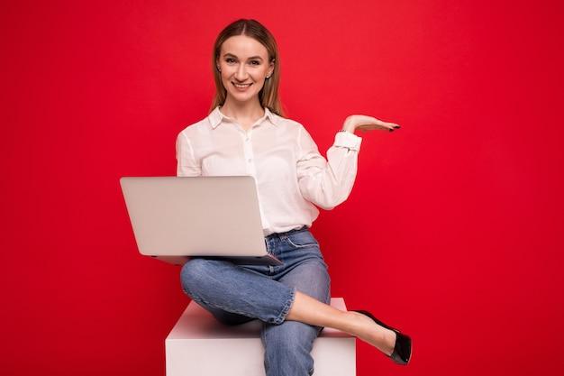 Молодая женщина в белой рубашке делает видеозвонок с ноутбука на красном фоне