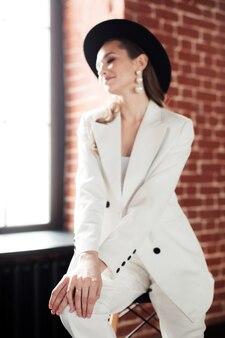 白いスーツと黒い帽子の若い女性