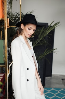 Молодая женщина в белом костюме и черной шляпе