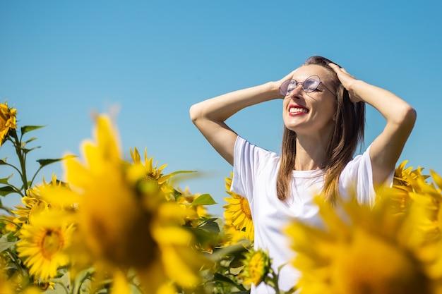 白いtシャツとメガネの若い女性は夏にひまわり畑で日光浴をします