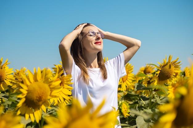 白いtシャツとメガネの若い女性がひまわり畑で日光浴をします