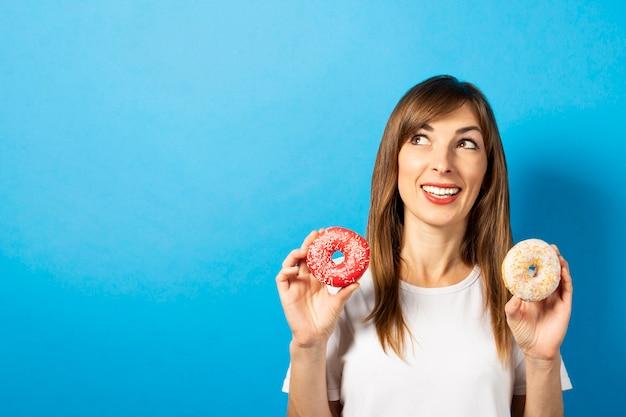 白いtシャツの若い女性は孤立したドーナツを保持します。