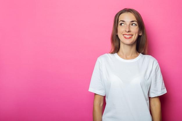 Молодая женщина в белой футболке смотрит в сторону на розовом