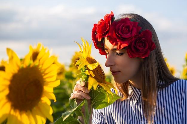 赤い花の花輪の若い女性は、日没時にひまわり畑でひまわりを嗅ぎます。