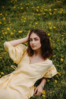 タンポポと緑の草のフィールドで黄色のドレスを着た若い女性