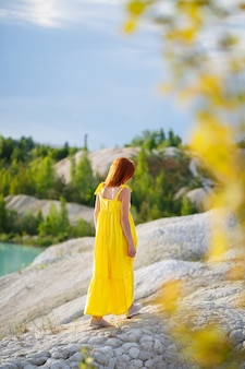 紺碧の水と緑の木々と湖の近くの黄色のドレスを着た若い女性。