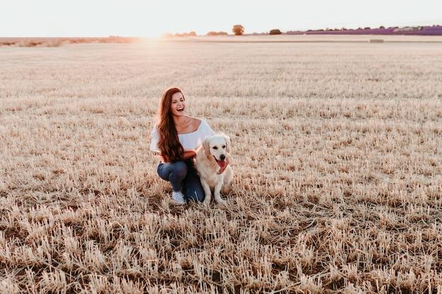 夕暮れ時の彼女のゴールデンレトリーバー犬と黄色のフィールドの若い女性。屋外のペット
