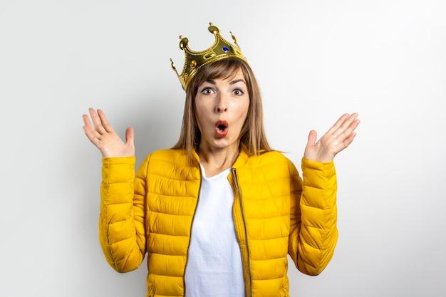 Молодая женщина в желтой куртке и короне на голове с удивленным лицом