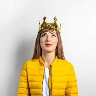 Молодая женщина в желтой куртке и золотой короне на светлом фоне.