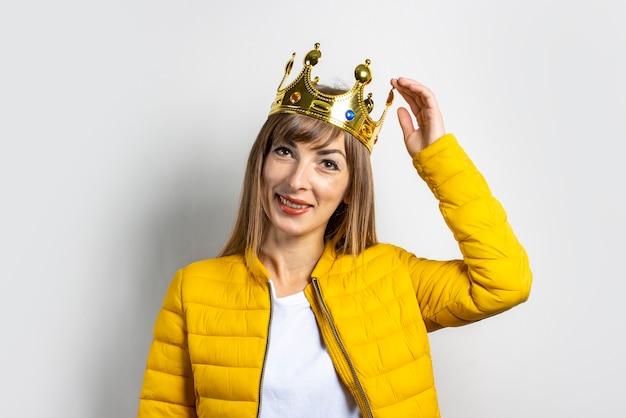 Молодая женщина в желтом пиджаке и золотой короне