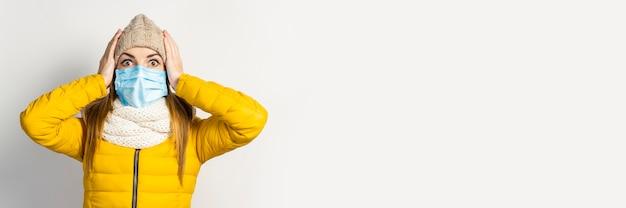 分離された医療マスクと黄色のジャケットと帽子の若い女性
