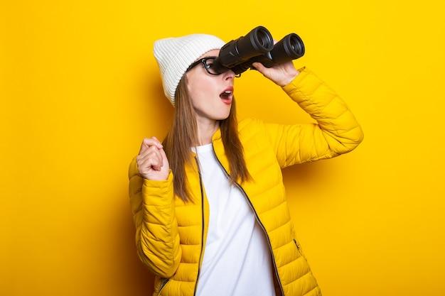 Молодая женщина в желтой куртке удивленно смотрит в бинокль на желтой поверхности Premium Фотографии