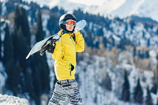그녀의 어깨에 스노우 보드와 함께 노란색 재킷에 젊은 여자는 스키 슬로프를 본다
