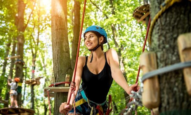 Молодая женщина в веревочном парке приключений. альпинистское снаряжение. ношение ремня безопасности и защитных шлемов.