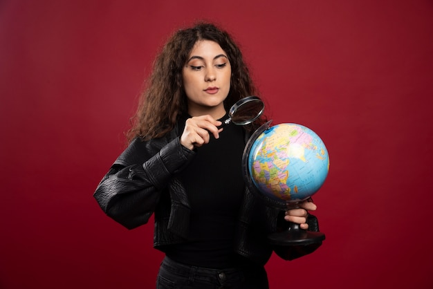 부분 확대 지구본을 들고 모든 검은 옷에 젊은 여자.