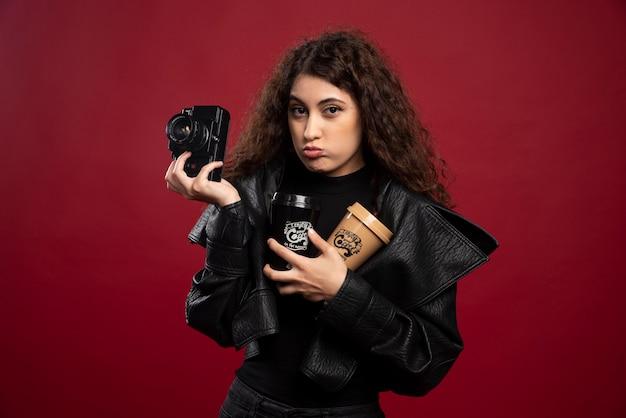 Молодая женщина во всем черном наряде держит чашки и фотоаппарат.