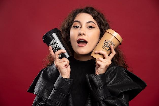 Молодая женщина в черном костюме держит две чашки.