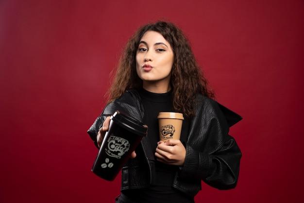 Молодая женщина во всем черном наряде показывает две чашки.