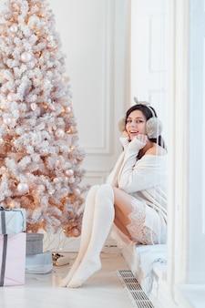 크리스마스 트리 근처 우아한 드레스에 젊은 여자