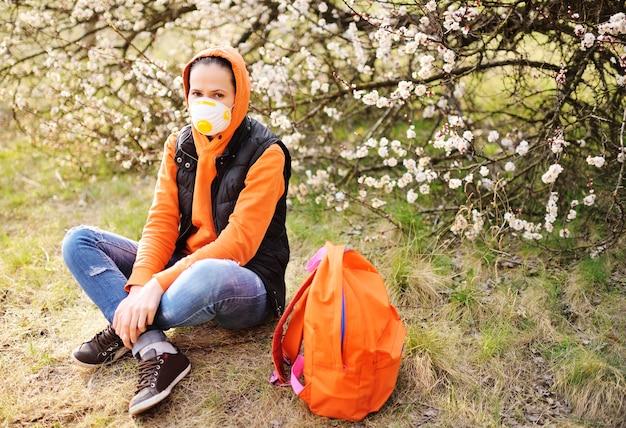 인공 호흡기 또는 마스크가 달린 주황색 후드 티셔츠를 입은 젊은 여성
