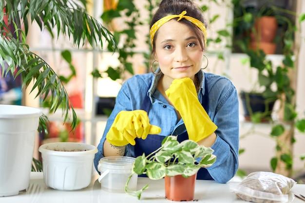 앞치마와 고무 장갑을 끼고 식물을 이식할 준비를 하는 카메라를 바라보는 젊은 여성