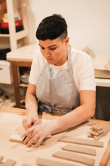 木製のテーブルにツールで粘土を切るエプロンの若い女性
