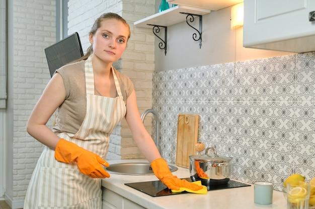 Молодая женщина в фартуке, перчатки, чистящая стиральную плиту с тряпкой