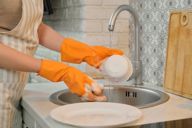 Молодая женщина в перчатках фартука моет посуду губкой и моющим средством