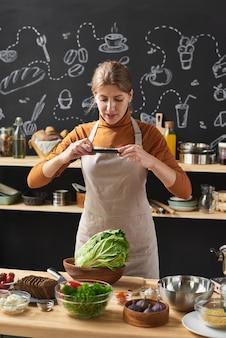 부엌에 서있는 그녀의 휴대 전화에 그릇에 신선한 야채의 사진을 만드는 앞치마에 젊은 여자