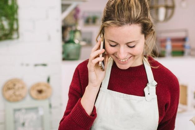 スマートフォンで話すエプロンの若い女性