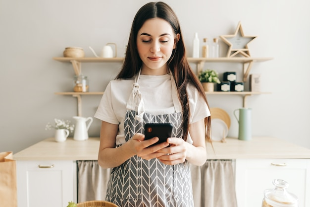 Молодая женщина в фартуке использует смартфон на кухне
