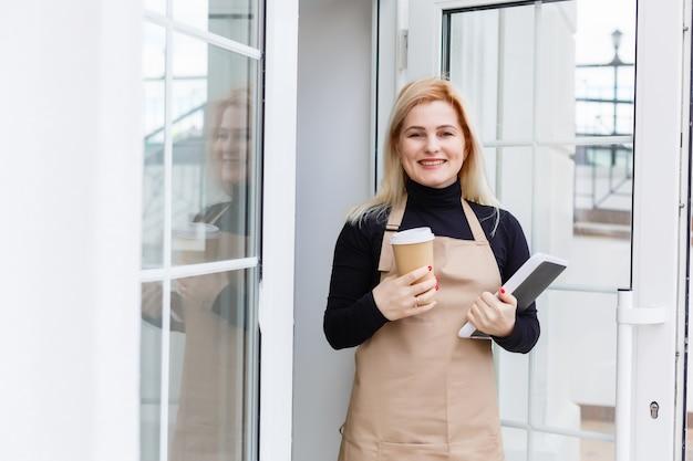灰色の背景にコーヒーを飲みながらエプロンの若い女性。バリスタのコンセプト
