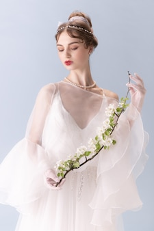 흰 벽에 고립 된 예술 행동에 젊은 여자. 레트로 스타일, 시대 개념의 비교. 공주, 여왕 또는 공작 부인과 같은 아름다운 여성 모델, 구식.