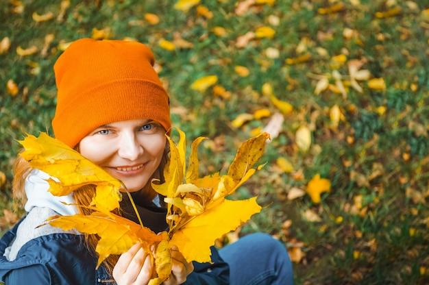 Молодая женщина в осенней одежде, держа букет осенних желтых листьев. открытый.