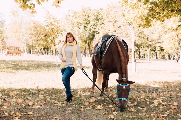 Молодая женщина в осеннем парке в солнечный день гуляет с лошадью