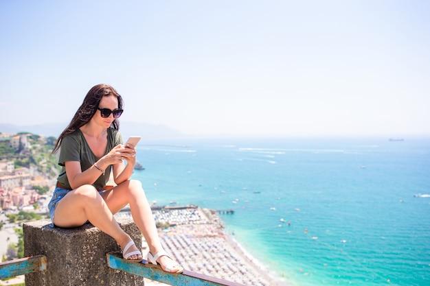 地中海と空を背景に若い女性。