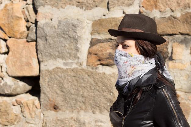 トレンディな帽子と革のジャケットで彼女の下の顔の周りに結ばれたバンダナを身に着けているバンディットスタイルのファッションの若い女性、石の壁の前の側面図